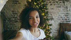 Młoda amerykanin afrykańskiego pochodzenia dziewczyna gawędzi online rozmowę używać smartphone kamerę w domu blisko choinki zbiory wideo