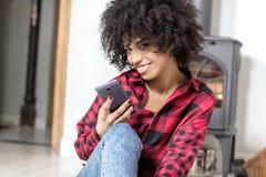 Młoda amerykanin afrykańskiego pochodzenia dziewczyna z telefonem komórkowym Zdjęcia Royalty Free