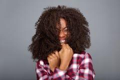 Młoda amerykanin afrykańskiego pochodzenia kobieta śmia się z włosianym nakryciem jej twarz zdjęcie stock