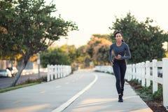 Młoda amerykanin afrykańskiego pochodzenia kobieta biega przy ogrodzenie w Obrazy Stock