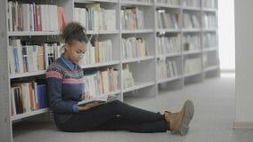 Młoda amerykanin afrykańskiego pochodzenia kobieta jest czytelniczej książki obsiadaniem na podłodze w szkolnej bibliotece
