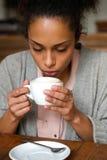 Młoda amerykanin afrykańskiego pochodzenia kobieta pije filiżankę kawy Zdjęcie Royalty Free