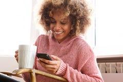 Młoda amerykanin afrykańskiego pochodzenia kobieta pije gorącą filiżankę kawy i patrzeje telefon komórkowego obrazy stock