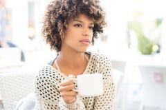 Młoda amerykanin afrykańskiego pochodzenia kobieta pije kawę Obraz Stock