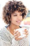 Młoda amerykanin afrykańskiego pochodzenia kobieta pije kawę Fotografia Royalty Free