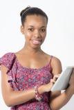 Młoda amerykanin afrykańskiego pochodzenia kobieta pisać na maszynie na jej pastylce Obrazy Royalty Free