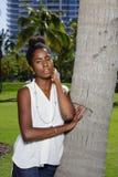 Młoda amerykanin afrykańskiego pochodzenia kobieta pozuje drzewko palmowe szyi toching włosy w babeczce fotografia royalty free