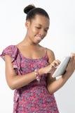 Młoda amerykanin afrykańskiego pochodzenia kobieta pracuje na jej pastylce Obraz Royalty Free