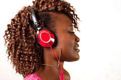 Młoda amerykanin afrykańskiego pochodzenia kobieta słucha muzyka  zdjęcia royalty free