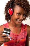 Młoda amerykanin afrykańskiego pochodzenia kobieta słucha muzyka z hełmofonami Zdjęcia Stock
