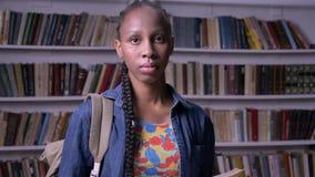 Młoda amerykanin afrykańskiego pochodzenia kobieta z plecak czytelniczą książką w bibliotecznej, patrzeje kamerze i, zdjęcie wideo
