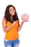 Młoda amerykanin afrykańskiego pochodzenia kobieta z prosiątko bankiem Zdjęcie Royalty Free