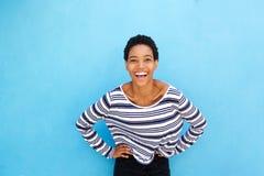 Młoda amerykanin afrykańskiego pochodzenia młoda kobieta ono uśmiecha się przeciw błękit ścianie Fotografia Royalty Free