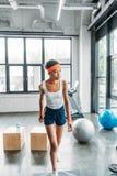 młoda amerykanin afrykańskiego pochodzenia sportsmenka ćwiczy na krok platformie w kapitałce i wristbands fotografia stock