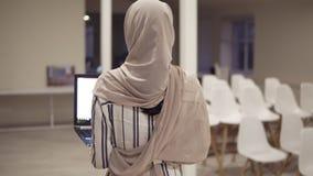 Młoda arabska żeńska kobieta jest ubranym hijab iść salą podczas gdy trzymający jej czarnego laptop w rękach Pracownik, pracuje zbiory wideo