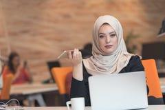 Młoda Arabska biznesowa kobieta jest ubranym hijab, pracuje w jej początkowym biurze zdjęcie stock