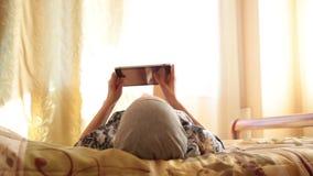 Młoda arabska dziewczyna z pastylka komputeru osobistego komputerem na łóżko sypialni w domu kobieta odbijająca w ekranie Technol zbiory