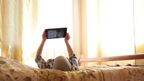 Młoda arabska dziewczyna z pastylka komputeru osobistego komputerem na łóżko sypialni w domu kobieta odbijająca w ekranie Technol zdjęcie wideo