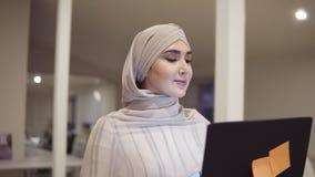 Młoda arabska kobieta jest ubranym hijab iść salą podczas gdy trzymający jej czarnego laptop w rękach Pracownik, pracujący miejsc zdjęcie wideo