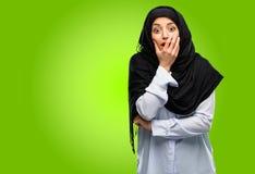 Młoda arabska kobieta jest ubranym hijab odizolowywającego nad zielonym tłem obraz royalty free