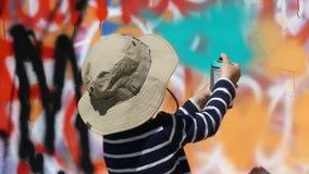 Młoda artysta chłopiec maluje kolorową ścianę zbiory