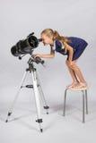 Młoda astronom pozycja na śmiesznym patrzeć w teleskopu eyepiece i krześle Obraz Stock