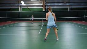 Młoda atleta bije z tenisowych piłek podczas szkolenia z ona partnerów, kobieta w sporta kostiumu aktywnie biega wokoło zbiory wideo