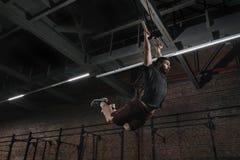 Młoda atleta robi Ups na gimnastycznych pierścionkach przy przecinającym dysponowanym gym Przystojnego mężczyzny ćwiczy mięsień u obraz stock