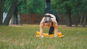 Młoda atlety kobieta Kłama na dywanie w parku na Zielonym gazonie w sporta strój Angażujący Ćwiczy joga zdjęcie wideo