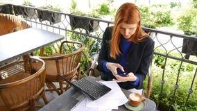 Młoda atrakcyjna biznesowa kobieta używa laptop i telefon komórkowego z zieleń ekranem w kawiarni Dokumenty dalej i filiżanka kaw zbiory wideo