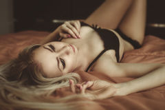 Młoda atrakcyjna blond kobieta w seksownej bieliźnie pozuje w łóżku. Vo Obraz Royalty Free