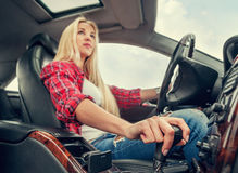 Młoda atrakcyjna blondynki dziewczyna jedzie samochód z automatycznym przekładni pudełkiem Zdjęcia Stock