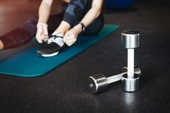 Młoda atrakcyjna brunetki dziewczyna enlacing jej sportów buty matuje po ćwiczyć treningu i crossfit szkolenie na błękitny joga obrazy stock