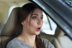 Młoda atrakcyjna caucasian kobieta jedzie samochód z grymasem zdziwienie lub szok za kołem, usta otwierający obrazy stock