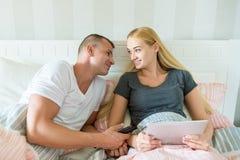 Młoda atrakcyjna caucasian para w łóżku Kobieta trzyma cyfrową pastylkę, obsługuje czule patrzeć ona, mieć nadzieję łapać jej uwa Zdjęcie Stock