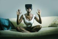 Młoda atrakcyjna czarna afro Amerykańska kobieta bawić się VR gogle słuchawki próbuje dotykać złudzenie przy żywą izbową leżanką Zdjęcie Royalty Free