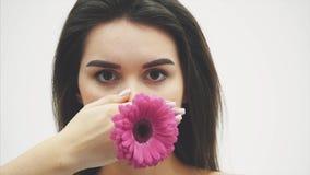 Młoda atrakcyjna dama na w górę białego tła Utrzymujący kwiatu w ręce podnosi je przy poziomem twarz zbiory wideo