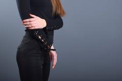 Młoda atrakcyjna dziewczyna jest ubranym czarnych spodnia i czarną bluzkę Obrazy Royalty Free