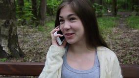 Młoda atrakcyjna dziewczyna mówi dzwonić na ławce chmury nad parkowymi lat białe drzewa uśmiech HD materiału filmowego mknąca sta zdjęcie wideo