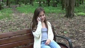 Młoda atrakcyjna dziewczyna mówi dzwonić na ławce chmury nad parkowymi lat białe drzewa uśmiech HD ruchu kamery mknąca panorama z zdjęcie wideo
