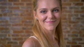 Młoda atrakcyjna dziewczyna ono uśmiecha się, patrzejący kamerę, portret, ściana z cegieł w tle