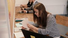 Młoda atrakcyjna dziewczyna używa laptop w nowożytnym początkowym biurze, pracujący z dokumentami, robi notatkom Fotografia Stock