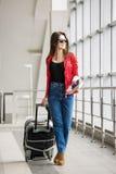 Młoda atrakcyjna dziewczyna w czerwonej kurtce z walizką iść na terminal W wszystkie przyroscie Fotografia Stock