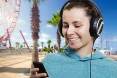 Młoda atrakcyjna dziewczyna z graczem słucha muzyka na miasto ulicie na jasnym słonecznym dniu zdjęcia royalty free