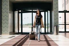 Młoda atrakcyjna dziewczyna z walizką iść na terminal Obrazy Royalty Free