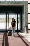 Młoda atrakcyjna dziewczyna z walizką iść na terminal Obraz Stock