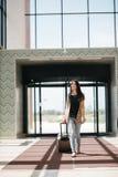 Młoda atrakcyjna dziewczyna z walizką iść na terminal Obrazy Stock