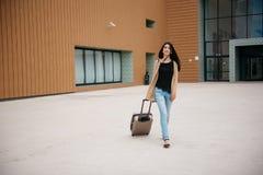 Młoda atrakcyjna dziewczyna z walizką iść na terminal Zdjęcia Stock