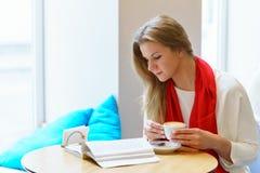 Młoda atrakcyjna europeang kobieta z czerwonym szalikiem czyta niektóre książkę blisko do okno i trzyma filiżankę cappuccino Zdjęcia Royalty Free