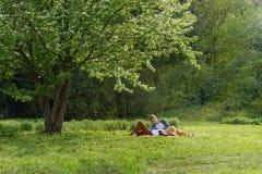 Młoda atrakcyjna europejska para z małym psem dostaje odpoczynek na koc w niektóre lato parku przy ciepłym słonecznym dniem piękn Fotografia Stock